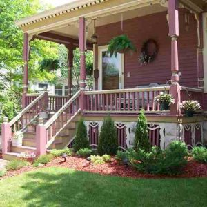 Front porch of pink Victorian home