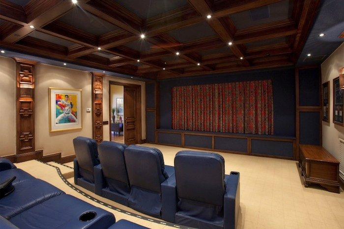 A 9+ person theater room with detailed wood ceiling.