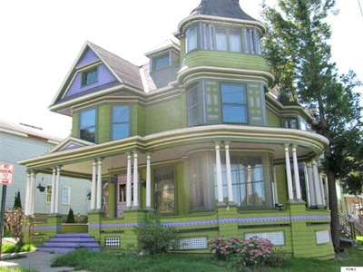 Victorian home accented in purple for sale in new york for Modern homes with wrap around porches