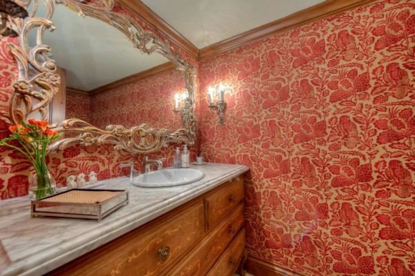 Bathroom with ornate mirror and orange wallpaper