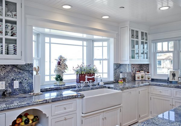Kitchen in Beach house in Ventura CA that was for sale. Persa Blue granite counters. Check out the ceiling and bay window above the sink. I adore the little touches like the blue and white dishes. The darling lower open shelving and I see a silver rooster paper towel holder that matches the farmhouse sink faucets.