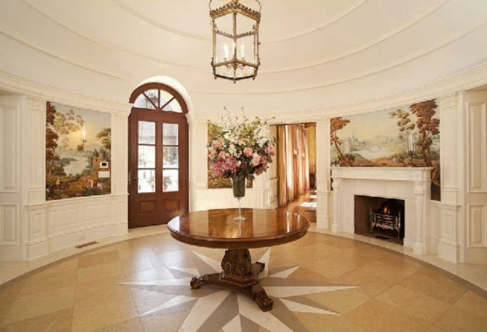 Rotunda entryway with marble floors, murals and marble top fireplace