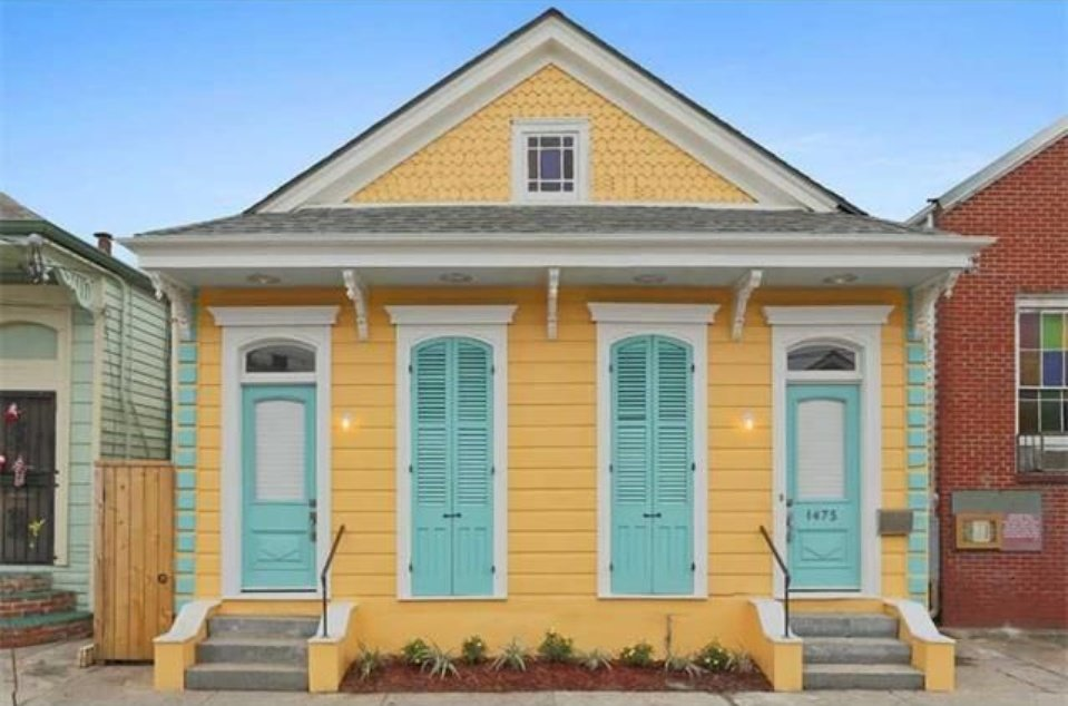 New Orleans house painted yellow with turquois shutters