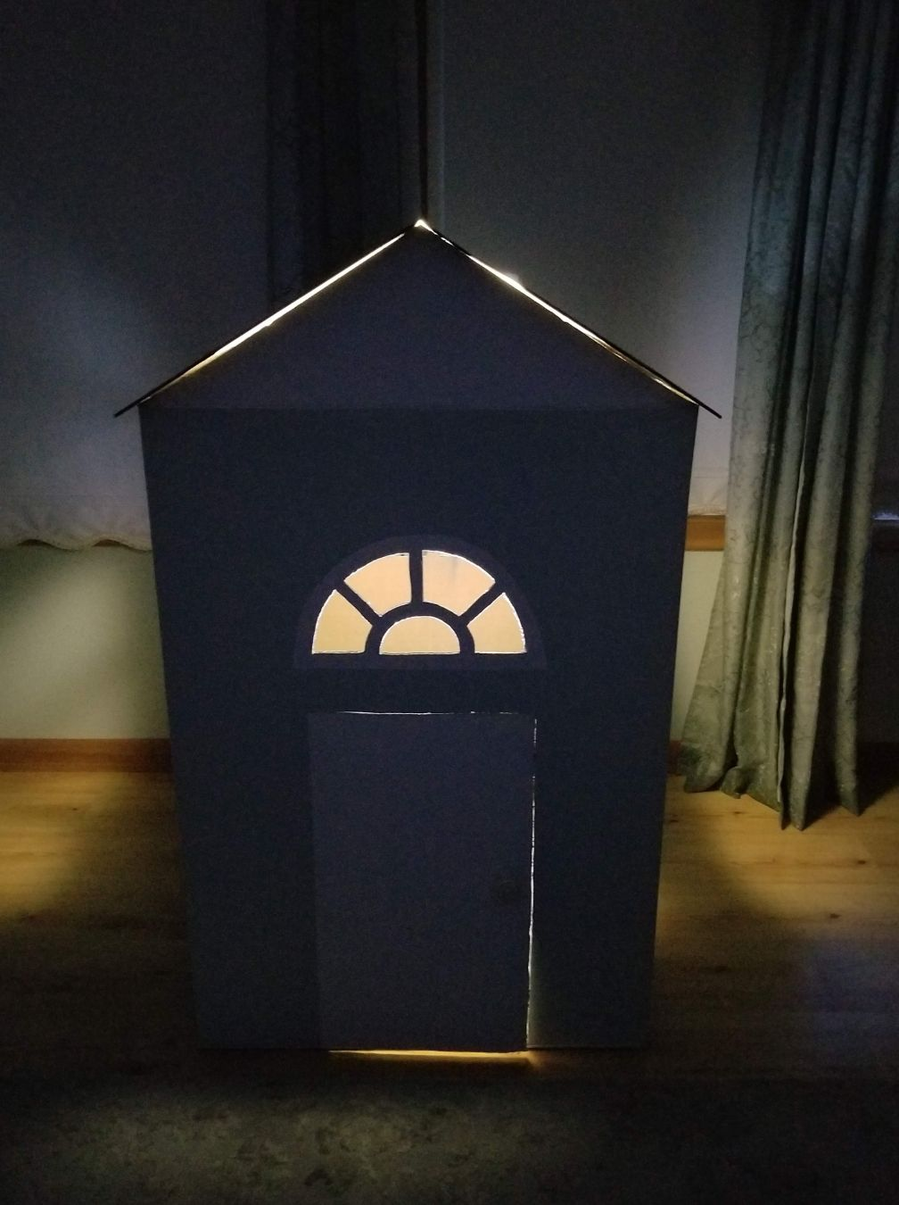 Cardboard Playhouse lit up at night
