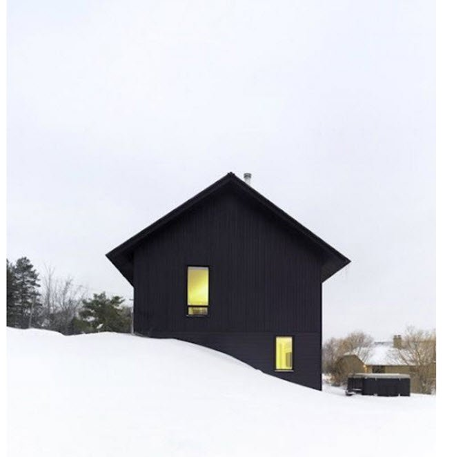 Black house in snow looks like a black arrow sticking out of the snow.