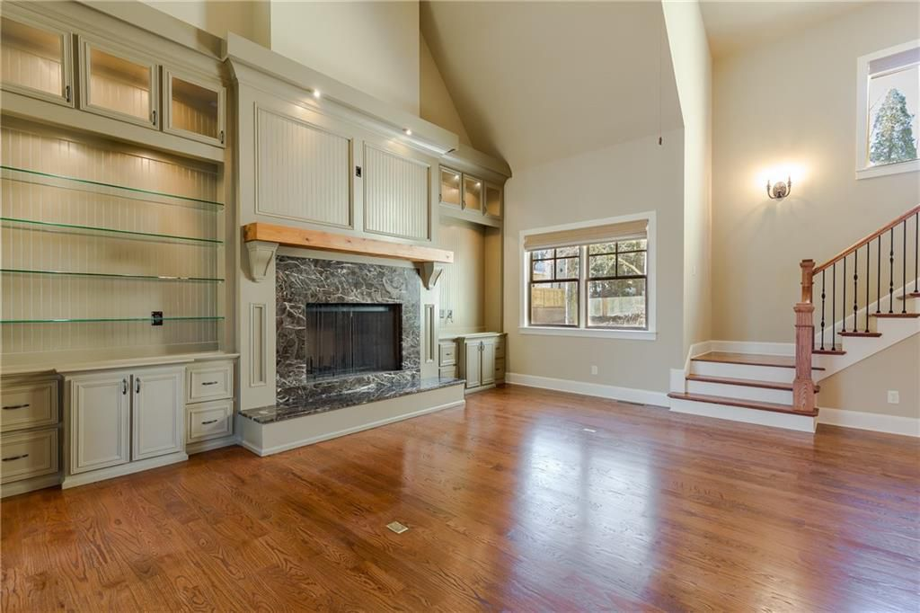 Family room with cathedral ceiling, fireplace and shelving