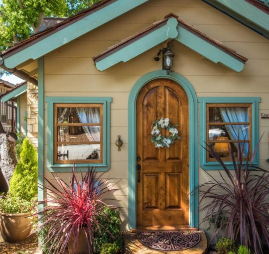 Cottage By The Sea Casa Carmela Entrance with arched wooden door and teal trim