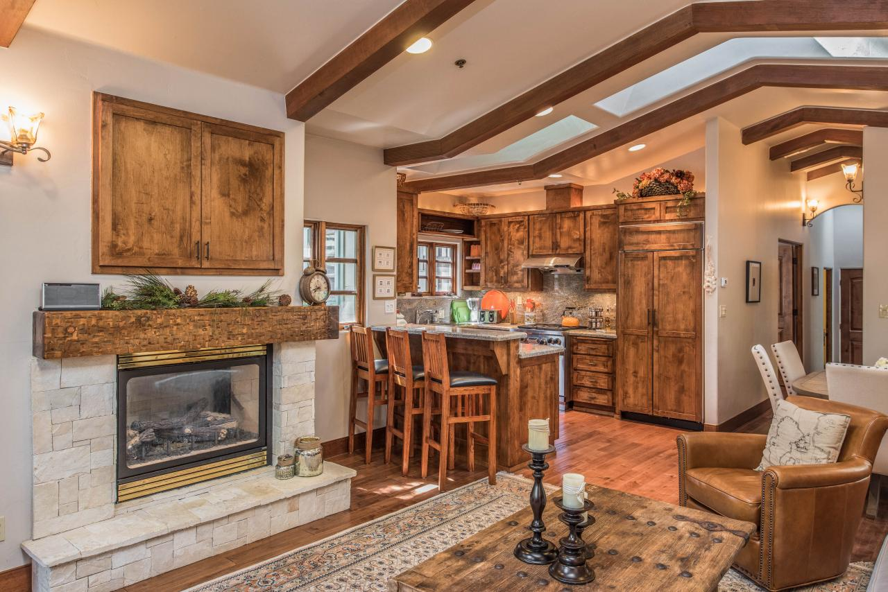 Cottage with concealed TV above white stone fireplace.