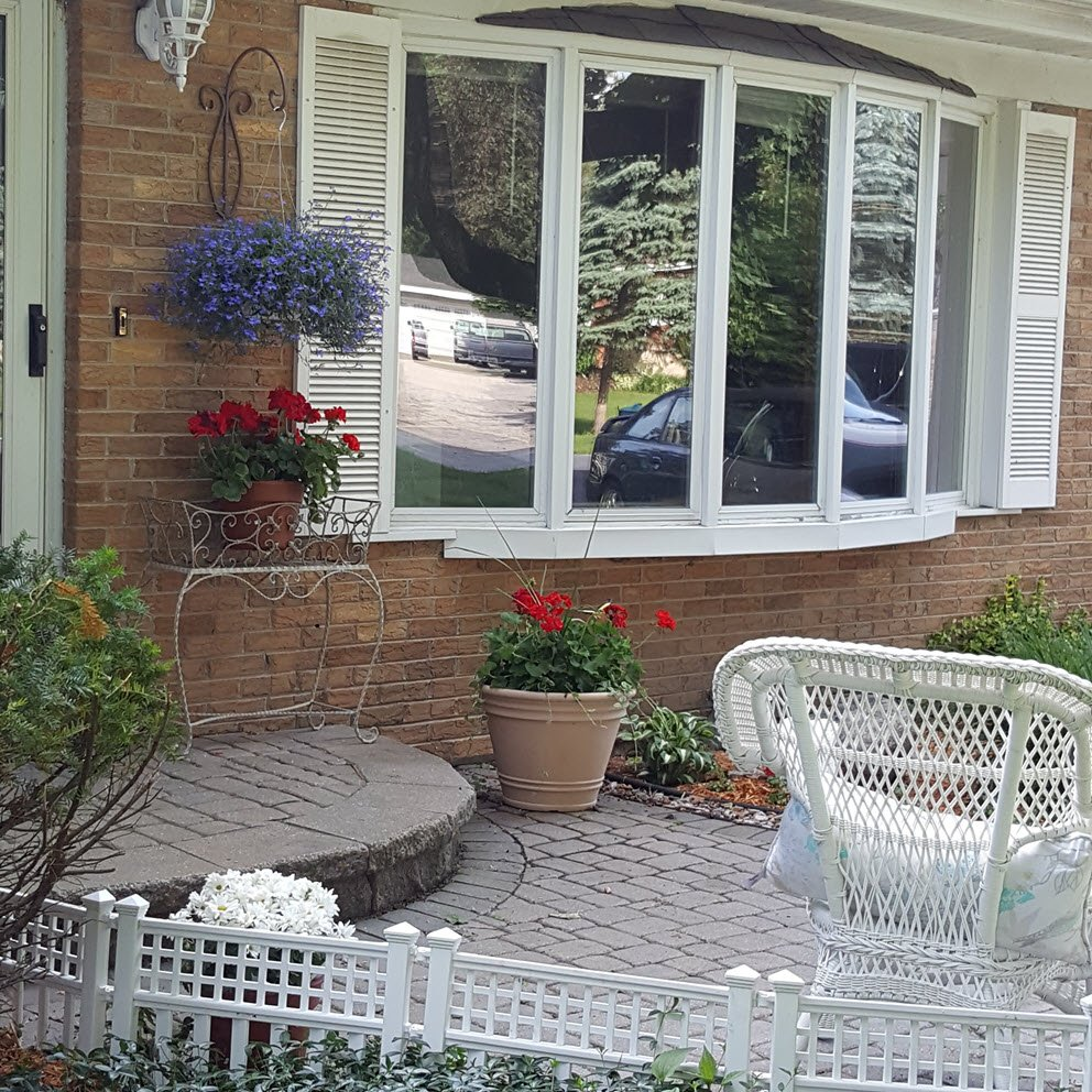 Curb appeal idea with a charming little white fence, hanging planters, flower pots and a wicker chair