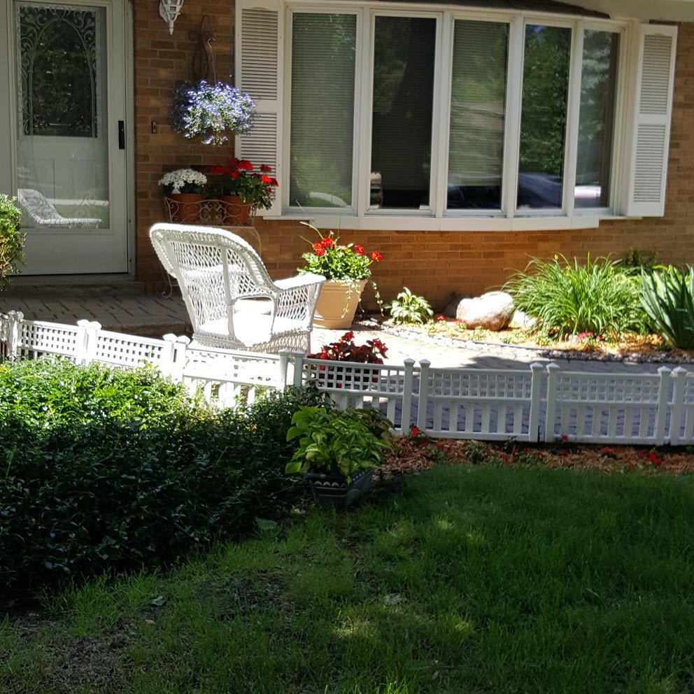 Charming curb appeal idea with little white fence, flowers and white wicker chair - Housekaboodle