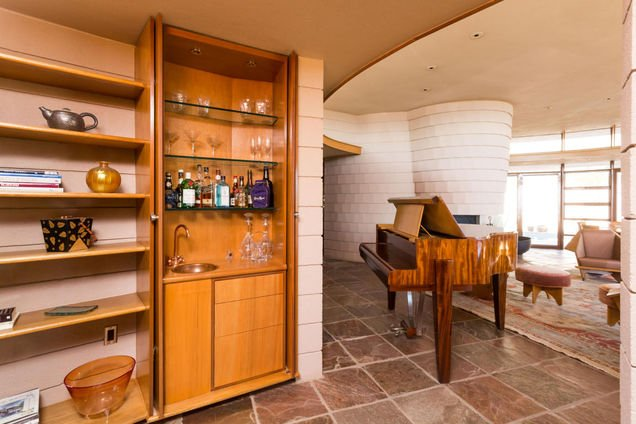 Enterrainment area - Frank Lloyd Wright house in AZ for sale has a lot of built-ins like this bar with hidden doors that close