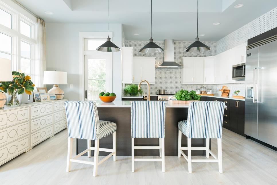 Kitchen with Thomas Counter Stools by Ethan Allen in the remodeled HGTV Dream Home beach house. Genius design of using two dressers under the windows.