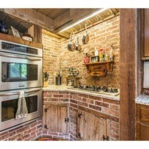 Kitchen with exposed brick and rustic wood cabinets - unique home for sale in West Chester PA