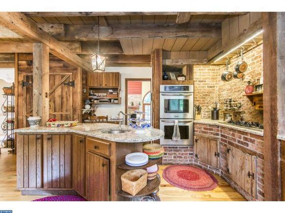 Kitchen with exposed brick, rustic wood cabinets and wood beams - West Chester PA
