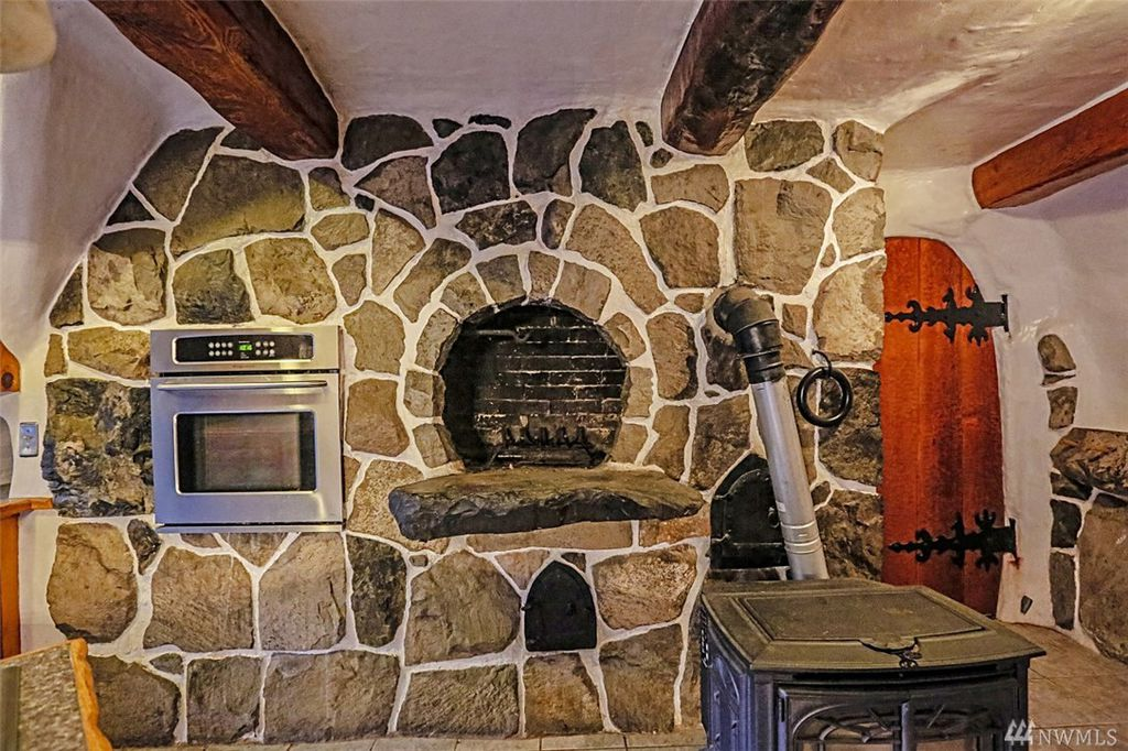 Kitchen with fairytale hearth fireplace in Snow White's cottage in Olalla WA for sale.
