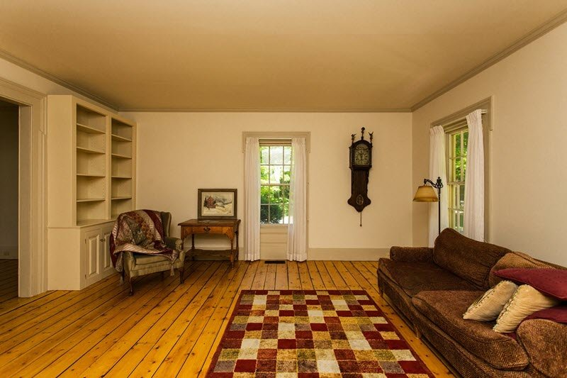 Living Room in Daley Colonial Farmhoue for sale in NY has antique pumpkin floors throughout