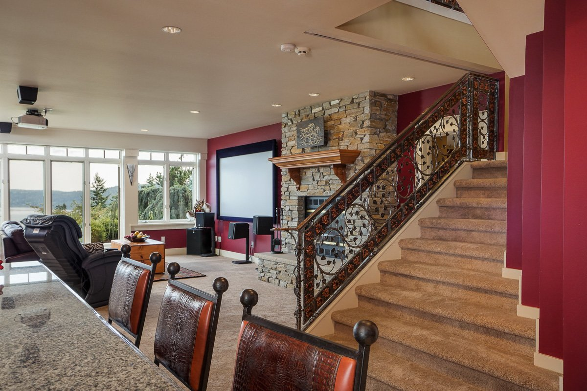 Lower level media room and bar with beautiful iron staircase