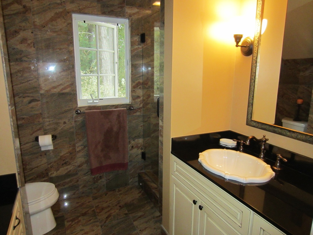 Master bath with shower and custom-shaped sink comes with the cozy cottage for sale