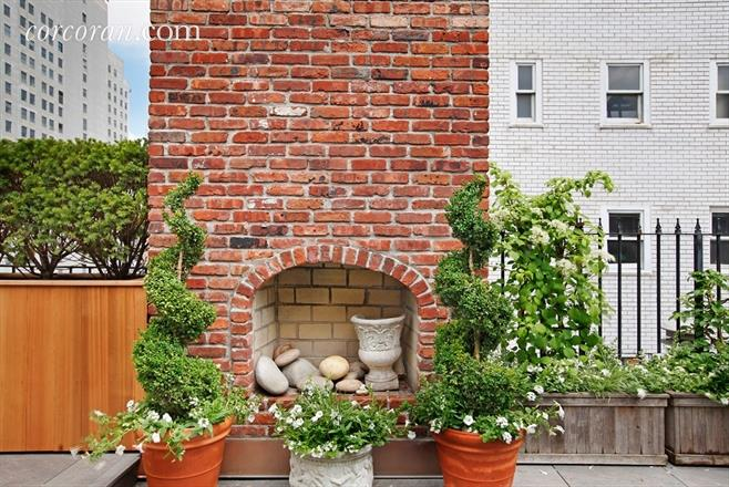 NYC ottage terrace fireplace is on the rooftop of a Condo