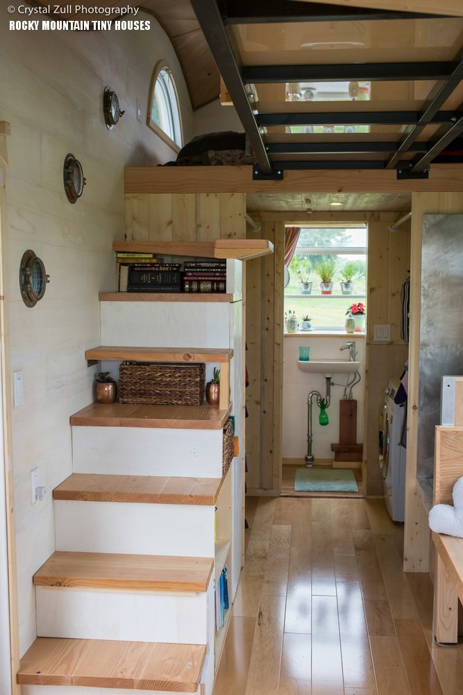 Pequod tiny house is custom-built with integraded storage in the stairs and solid brass porthole windows