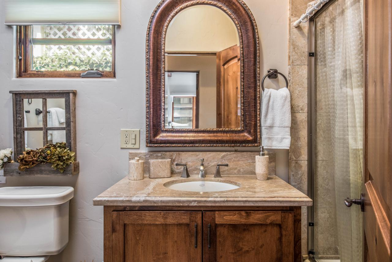 Second bath is a small cottage style bathroom with a lovely arched mirror