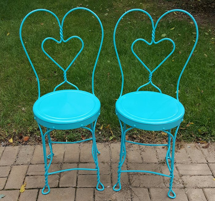 Two vintage ice cream parlor twisted wrought iron sweetheart chairs in seaside blue